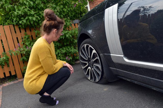 Foster carer Shelley Wheeldon inspects the damage to her car after a pothole accident in Kirkby.