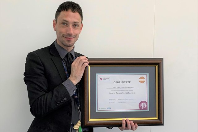 Tom Millar, deputy safeguarding lead and mental health lead at Queen's Elizabeth Academy, with the Young Carers in School' Award.