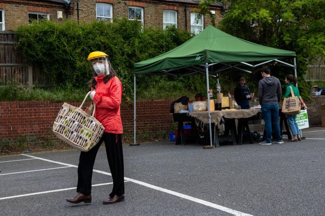 A woman wears a face shield, mask and gloves as she shops at Blackheath Farmers Market in London (Photo: Chris J Ratcliffe/Getty Images)