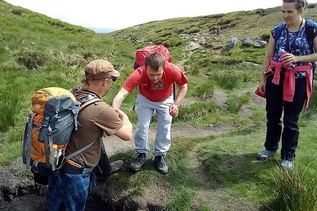 One of the young 'adventurers' being helped by an instructor on a break in the Peak District.