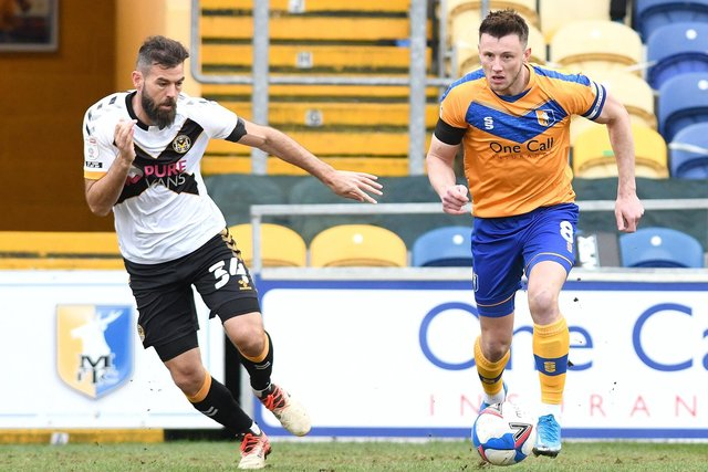 Mansfield's Ollie Clarke looks to find space away from Newport's Joe Ledley on Friday.