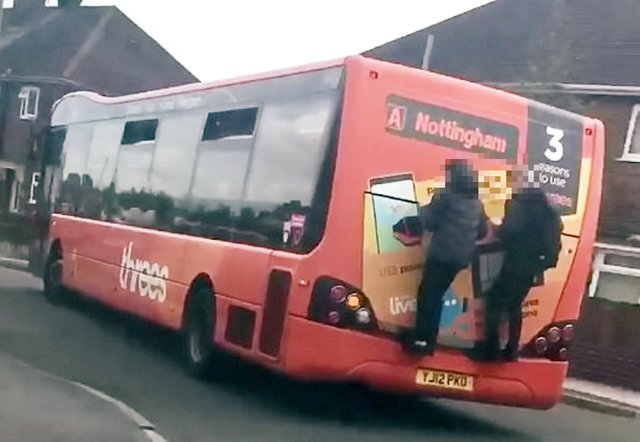 This is the shocking moment two reckless schoolboys hang on to the back of a bus for more than a minute before jumping off in Kirkby. Photo: Elizabeth Todd/SWNS