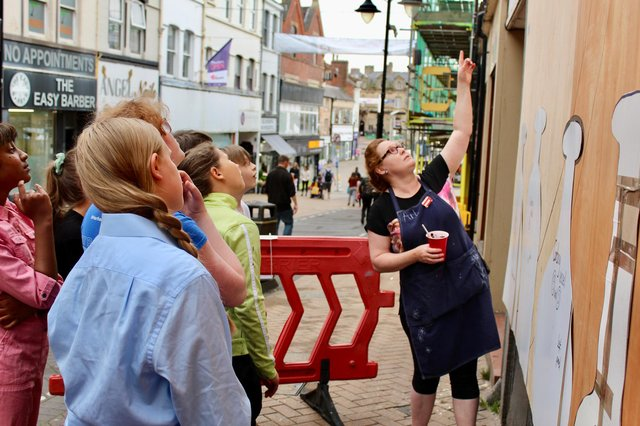 Artist Clare Taylor with students from Brunts Academy working on a temporary mural at an empty shop in Mansfield town centre