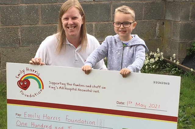 Jack Beard presenting the cheque for £120 to Clare Harris of the Emily Harris Foundation